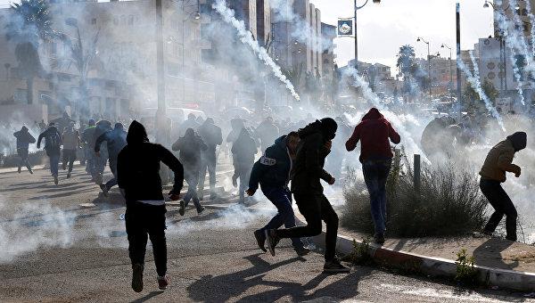 Палестинские протестующие бегут от слезоточивого газа, примененного израильскими войсками во время столкновений в знак протеста против решения президента США Дональда Трампа признать Иерусалим столицей Израиля, недалеко от еврейского поселения Бейт-Эль