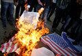 Палестинские демонстранты сжигают плакат с изображением президента США Дональда Трампа и флага США во время протеста против решения Трампа признать Иерусалим столицей Израиля в городе Газа