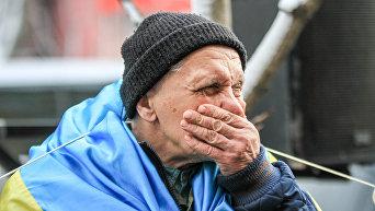 Пожилой мужчина с украинским флагом на плечах