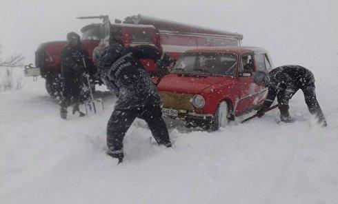 Спасатели вытаскивают из снежных заносов автомобили