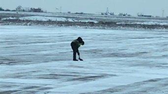 Сотрудник запорожского аэропорта чистит взлетную полосу от снега лопатой