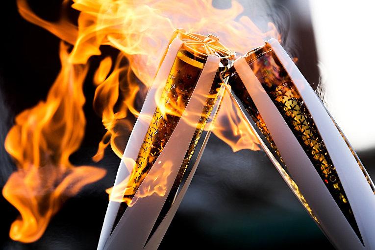 Факелы с Олимпийским огнём во время эстафеты Олимпийского огня XXIII зимних Олимпийских игр в Пхенчхане