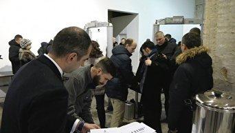 Работники Госуправления охраны проводят личный досмотр журналистов перед началом пресс-конференции Петра Порошенко