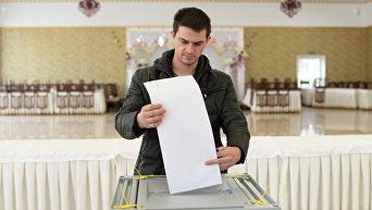 Молодой человек опускает бюллетень в урну на выборах президента РФ на избирательном участке в Бахчисарае