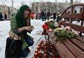 Женщина зажигает свечу возле здания торгового центра Зимняя вишня в Кемерово