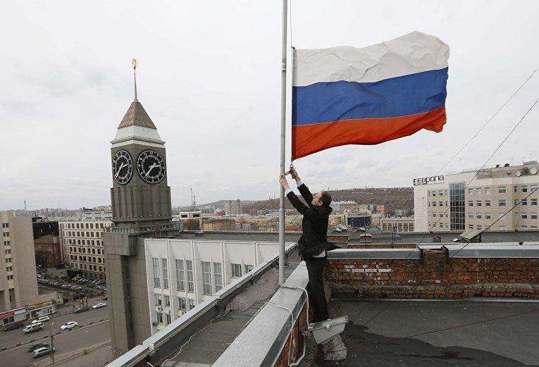 Сотрудник понижает флаг на половину мачты на крыше здания городской администрации в день национального траура для жертв пожара в торговом центре в Кемерово в Красноярске