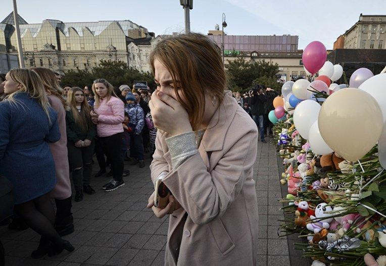Женщина плачет во время траурных мероприятий в память о погибших во время пожара в торговом центре  в Кемерово