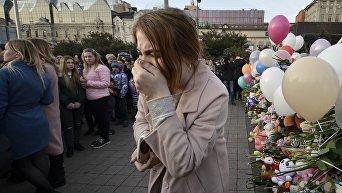 Женщина плачет во время траурных мероприятий в память о погибших во время пожара в Кемерово
