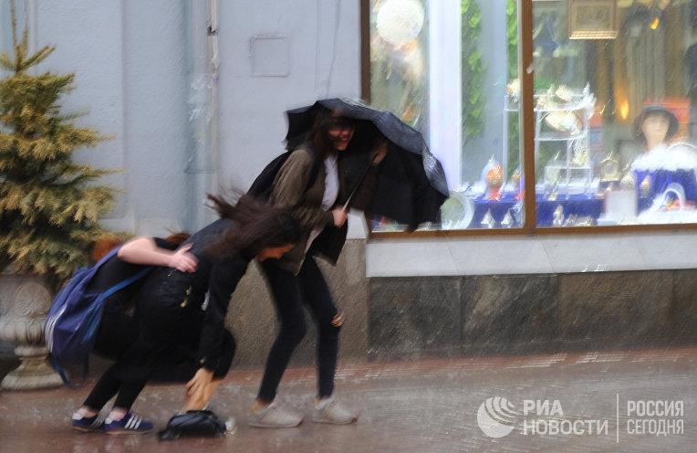 Пешеходы на улице в Москве во время сильного дождя