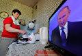 Жительница Москвы смотрит трансляцию церемонии инаугурации избранного президента России Владимира Путина