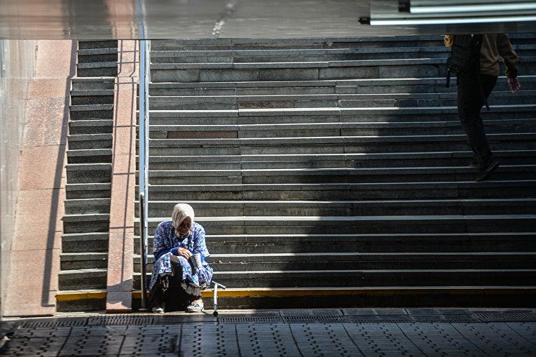 Женщина просит милостыню в подземном переходе в Киеве