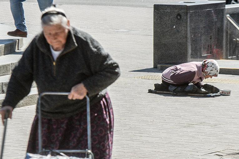 Женщина просит милостыню в центре Киева