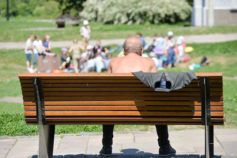 Мужчина сидит на скамейке в центре Киева