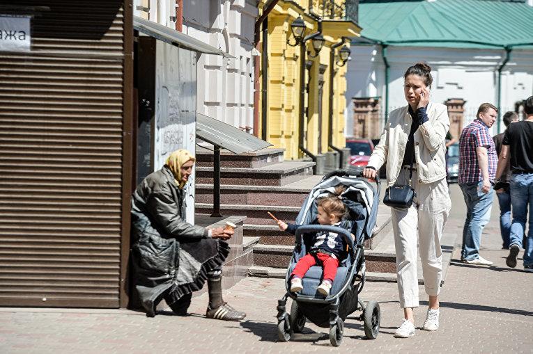 Молодая женщина с ребенком проходит мимо женщины, которая просит милостыню на центральной улице Киева