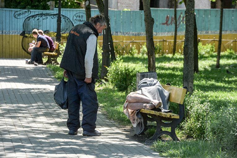 Бездомная женщина спит на скамейке на Подоле в Киеве