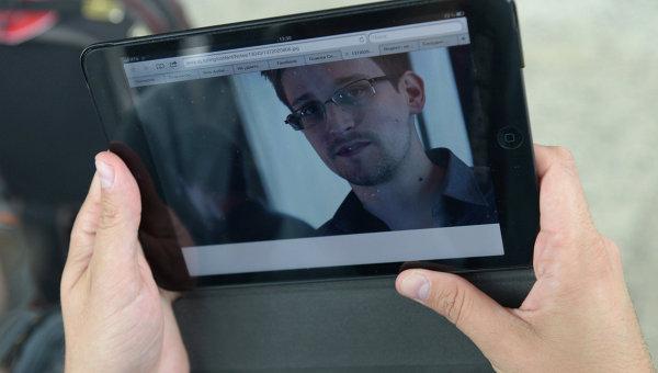 Журналист изучает фото Эдварда Сноудена