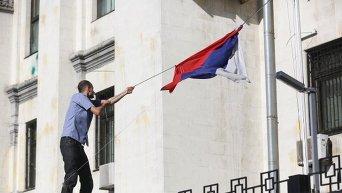 Активист срывает флаг РФ с посольства в Киеве