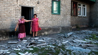 Местные жители стоят возле здания, где они живут, после обстрела в Донецке