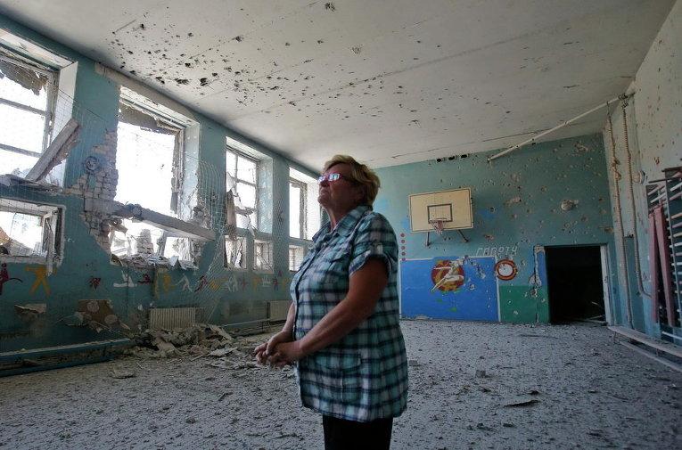 Преподаватель гимназии  осматривает повреждения в помещении  школы в селе Спартак