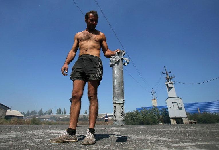 Мужчина демонстрирует остатки разорванного снаряда в селе Спартак