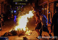 Прохожие идут мимо подожжённого мусора на улице Истикляль в Стамбуле