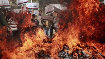 Жители Бенгази сжигают портреты Муаммара Каддафи, плакаты с его цитатами и Зеленую книгу Каддафи
