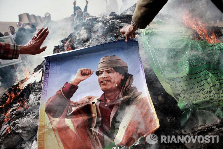 Житель Бенгази сжигает портрет Муаммара Каддафи