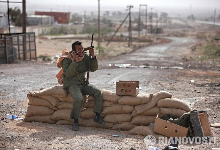 Боец с автоматом на блокпосту у дороги на въезде в восточноливийский город Марса-эль-Брега, контролируемый повстанцами