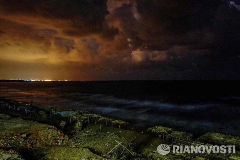 Пляж на побережье Средиземного моря и огни города Латакия