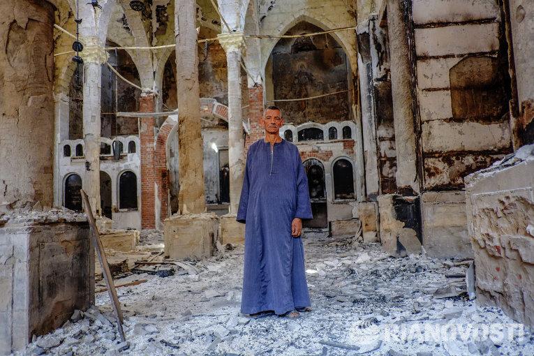 Копт в одной из сожженных и разрушенных коптских церквей в провинции Минья. Десятки храмов были сожжены и разрушены во время беспорядков в Египте