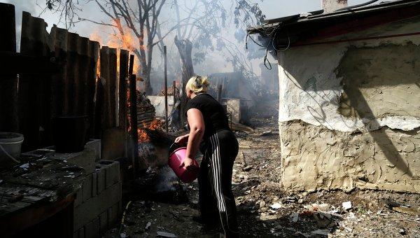 Местная жительница Донецка тушит пожар после обстрела
