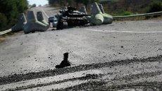 Солдатский ботинок у разбитого танка украинских военных близ села Лебединское