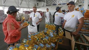 Волонтеры фасуют пакеты с гуманитарной помощью для беженцев из Донецкой области