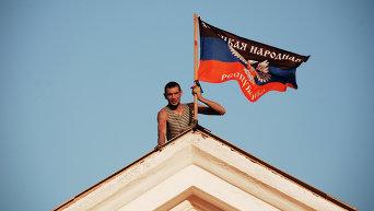 Ополченец устанавливает флаг ДНР. Архивное фото