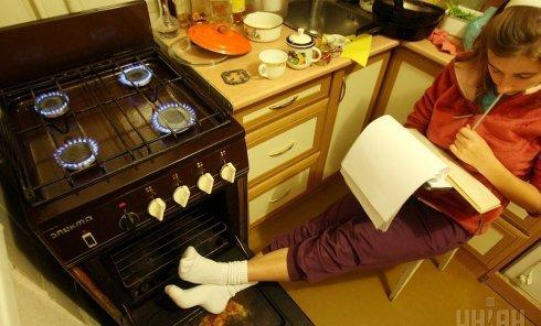 Девушка греется у газовой плиты