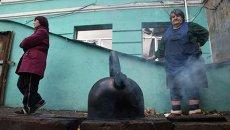 Люди кипятят воду недалеко от входа в бомбоубежище в Донецке