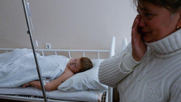 Оксана Сафонова возле своего сына Кирилла, пострадавшего при обстреле спортплощадки в Донецке