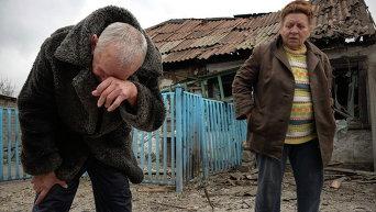 Местные жители у своего разрушенного дома в Донецке