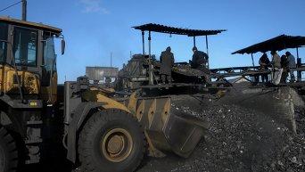 Рабочие занимаются сортировкой угля на нелегальной шахте в Торезе