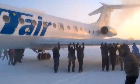 Пассажиры толкают самолет в аэропорту Игарки