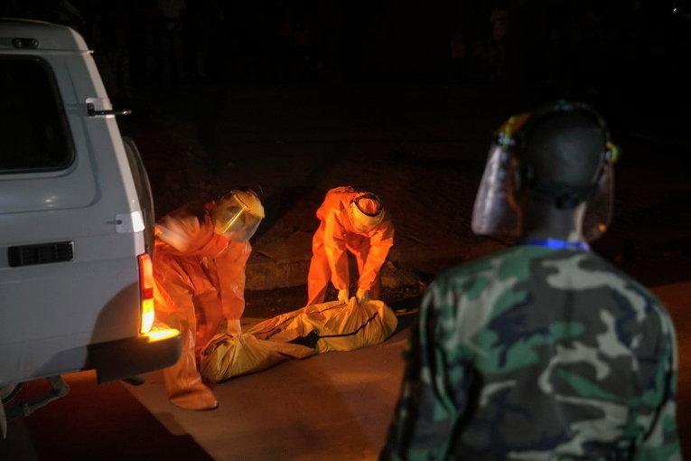 Медики забирают тело погибшего с улицы одного из городов Сьерра-Леоне