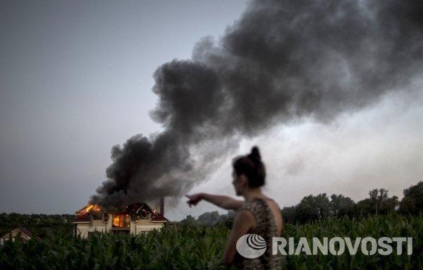 Загоревшийся в результате авиаобстрела дом в поселке Николаевка неподалеку от Луганска.