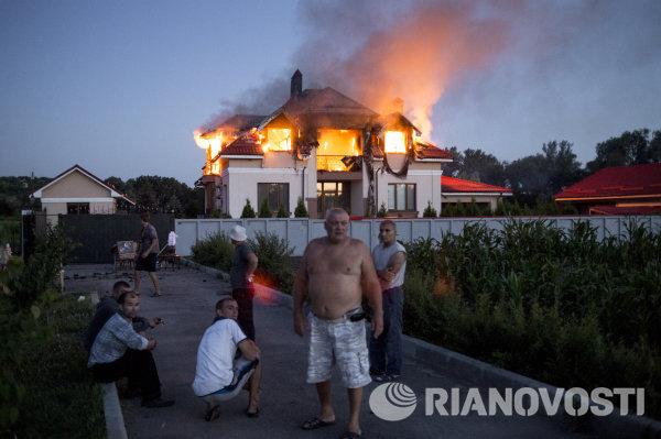 Жители соседних домов наблюдают за загоревшимся в результате авиаобстрела домом в поселке Николаевка неподалеку от Луганска.