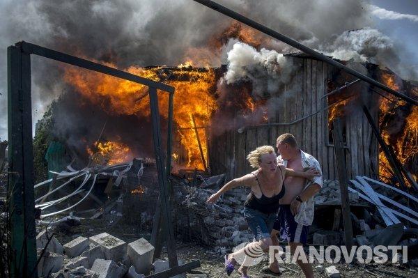 Местные жители спасаются от пожара, возникшего в результате авиационного удара
