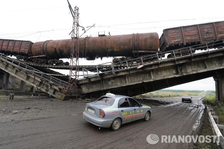 Автомобиль проезжает под взорванным железнодорожным мостом в районе Новобахмутовки и провисшим над ним грузовым составом.