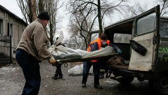 Мужчины загружают тело погибшего при обстреле в Донецке