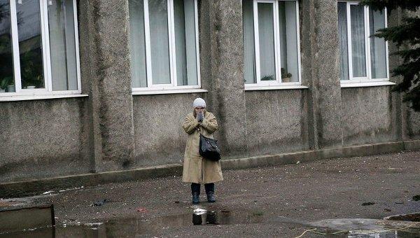 Женщина стоит возле обстрелянного здания администрации в Дебальцево