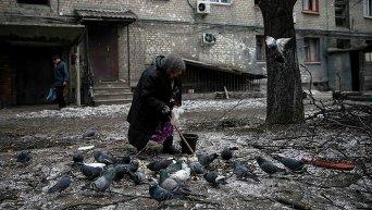 Пожилая женщина кормит голубей возле своего разрушенного дома в Дебальцево