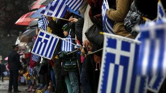 Греки под дождем смотрят военный парад во время празднования Дня независимости в Афинах