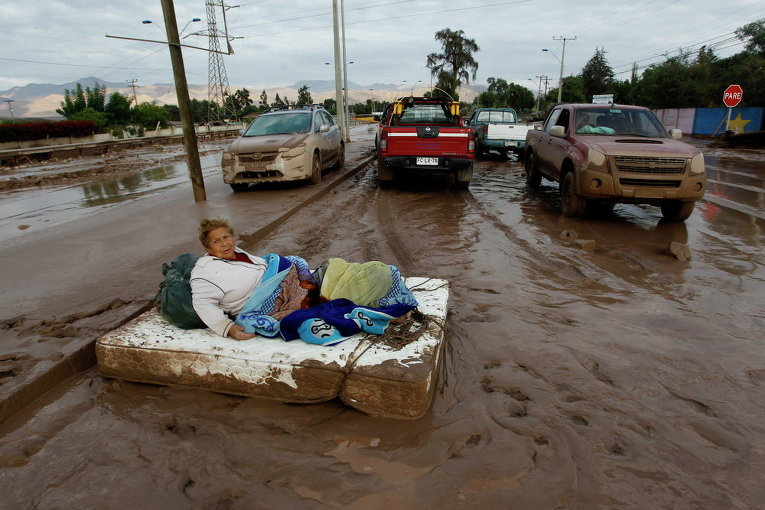 Женщина лежит на матраце на улице в грязи после ливней, которые вызвали сильные наводнения в Чили